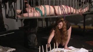 La donan in una gabbia nuda e sulle candele accese